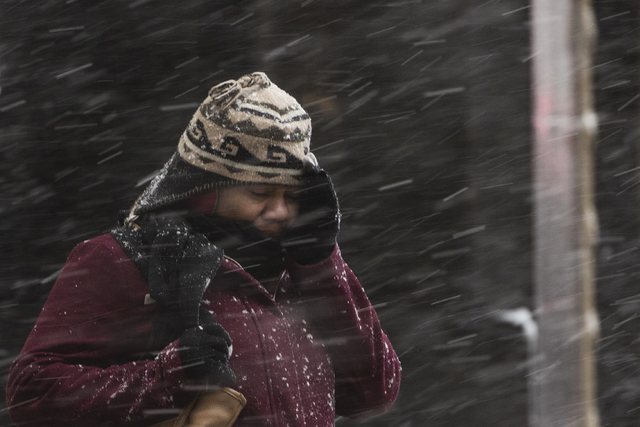 A woman shields her face during a winter storm in Philadelphia, Thursday, Feb. 9, 2017. A powerful, fast-moving storm swept through the northeastern U.S. Thursday, making for a slippery morning co ...