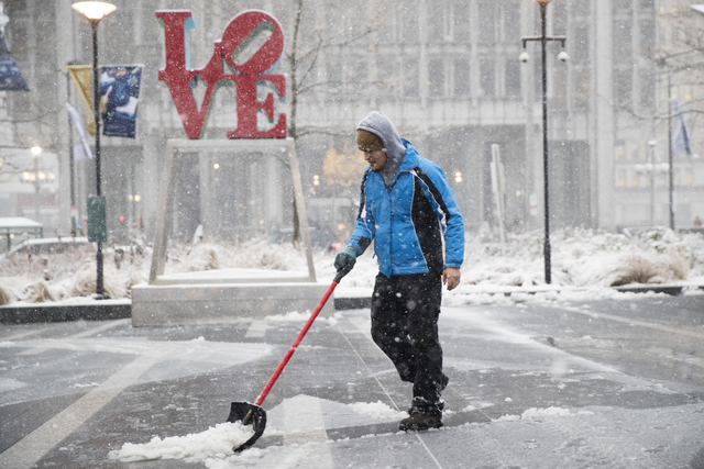 A man clears snow from Dilworth Park during a winter storm in Philadelphia, Thursday, Feb. 9, 2017. A powerful, fast-moving storm swept through the northeastern U.S. Thursday, making for a slipper ...