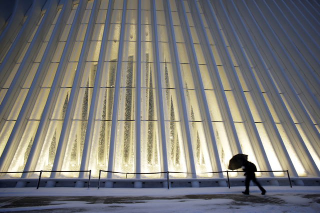 A man makes his way through wind and snow past the Oculus of the World Trade Center Transportation Hub, Thursday, Feb. 9, 2017, in New York. A powerful, fast-moving storm swept through the northea ...