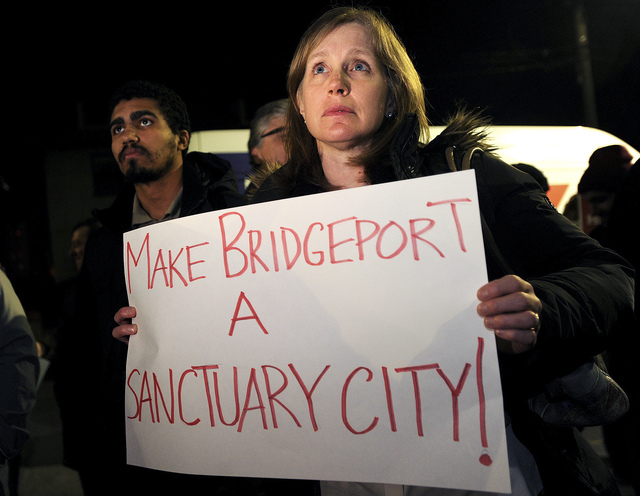 In this Monday, Feb. 6, 2017, file photo, Ann McCarthy, of Fairfield, attends a rally to make Bridgeport a sanctuary city outside City Hall in Bridgeport, Conn. Bridgeport Mayor Joe Ganim seized o ...