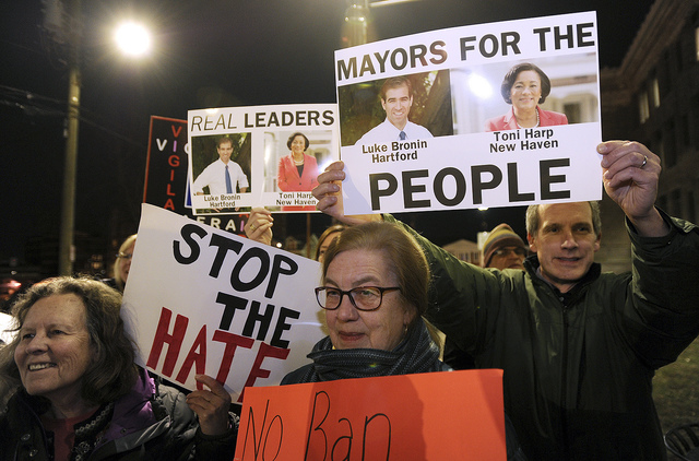 In this Monday, Feb. 6, 2017, file photo, people hold signs during a rally to advocating to make Bridgeport a sanctuary city outside City Hall in Bridgeport, Conn. Bridgeport Mayor Joe Ganim has q ...
