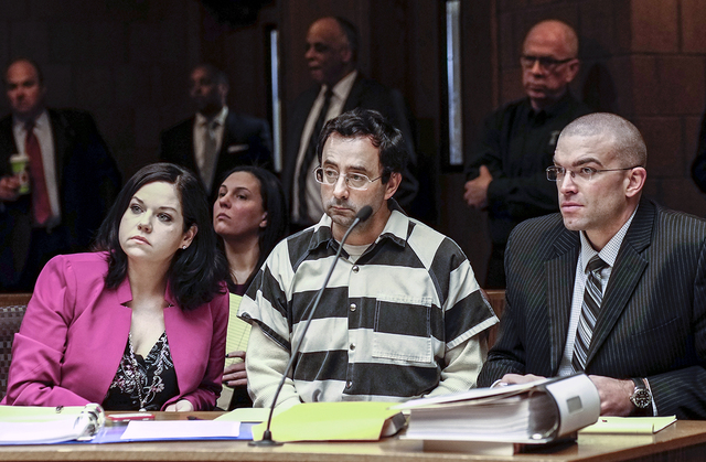 Dr. Larry Nassar, center, and his attorneys, Shannon Smith and Matt Newburg, listen to Judge Donald Allen Jr. rule that Nassar, a former Michigan State University and USA Gymnastics sports doctor, ...