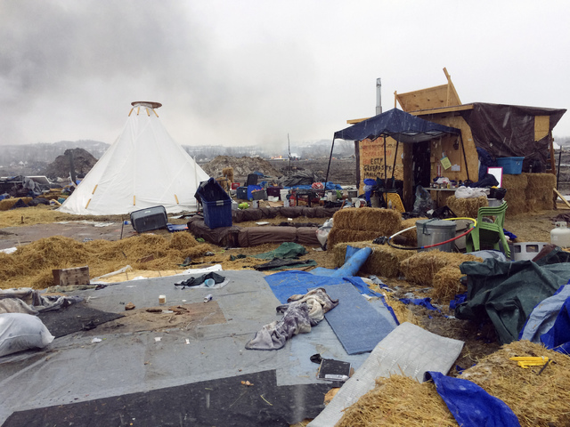 Refuse remains in the Dakota Access pipeline opponents' main protest camp as a fire burns in the background in southern North Dakota near Cannon Ball, N.D., on Wednesday, Feb. 22, 2017, as authori ...