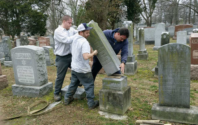 Rosenbloom Monument Co. workers from left, Nathan Fohne, Derek Doolin and Philip Weiss hoist a headstone at the Chesed Shel Emeth Cemetery in University City, Mo., where over 150 headstones were t ...