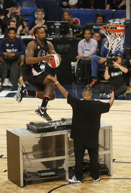 Los Angeles Clippers center DeAndre Jordan leaps over the turntable of DJ Khaled during the slam-dunk contest as part of the NBA All-Star Saturday Night events in New Orleans, Saturday, Feb. 18, 2 ...