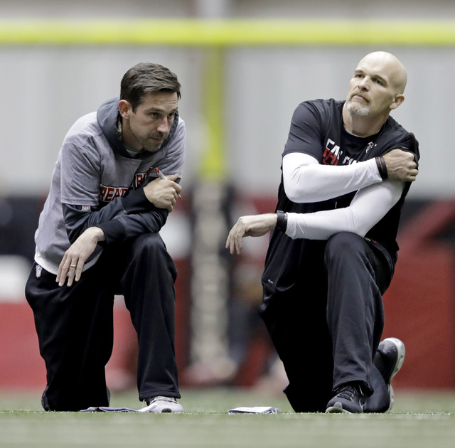 Atlanta Falcons head coach Dan Quinn, right, talks with offensive coordinator Kyle Shanahan during a workout at the NFL football team's practice facility in Flowery Branch, Ga., Friday, Jan. 27, 2 ...