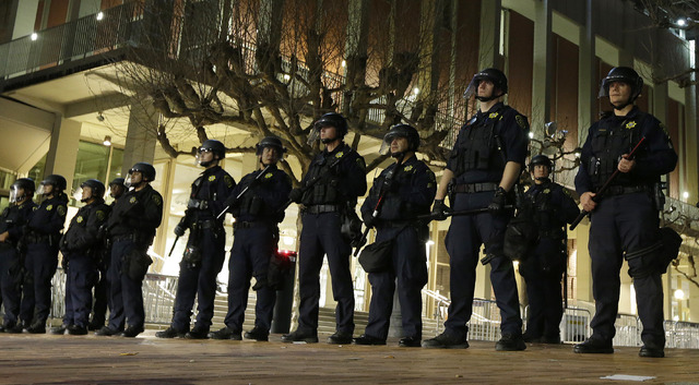 University of California at Berkeley police guard the building where Breitbart News editor Milo Yiannopoulos was to speak Wednesday, Feb. 1, 2017, in Berkeley, Calif. A small group of people with  ...