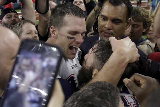 New England Patriots' Tom Brady congratulates a teammate after defeating the Atlanta Falcons in overtime at the NFL Super Bowl LI football game Sunday, Feb. 5, 2017, in Houston. The Patriots defea ...