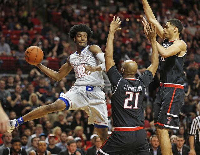 Kansas' Josh Jackson (11) passes the ball around Texas Tech's Anthony Livingston (21) and Zach Smith (11) during an NCAA basketball game Saturday, Feb. 11, 2017, in Lubbock, Texas. (Brad Tollefson/AP)