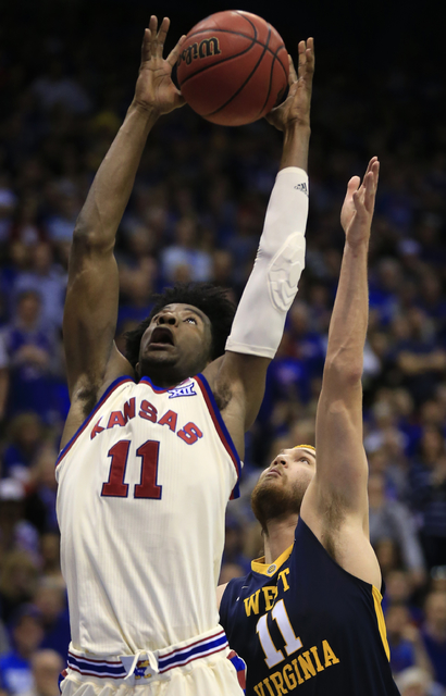 Kansas guard Josh Jackson, left, rebounds over West Virginia forward Nathan Adrian, right, during the second half of an NCAA college basketball game in Lawrence, Kan., Monday, Feb. 13, 2017. Kansa ...