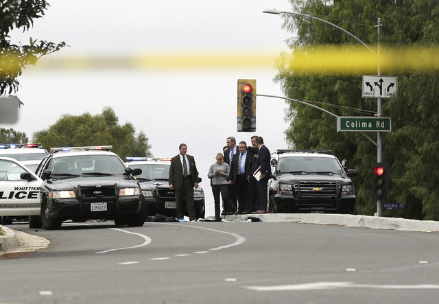 Authorities investigate the scene after a deadly shooting in Whitter, Calif., Monday, Feb. 20, 2017. A California police officer was killed and another wounded in a shooting Monday while they were ...