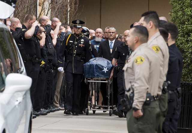 Officers salute during a procession for a fallen officer in Orange, Calif., Monday, Feb. 20, 2017. A California police officer was killed and another wounded in a shooting Monday while they were t ...