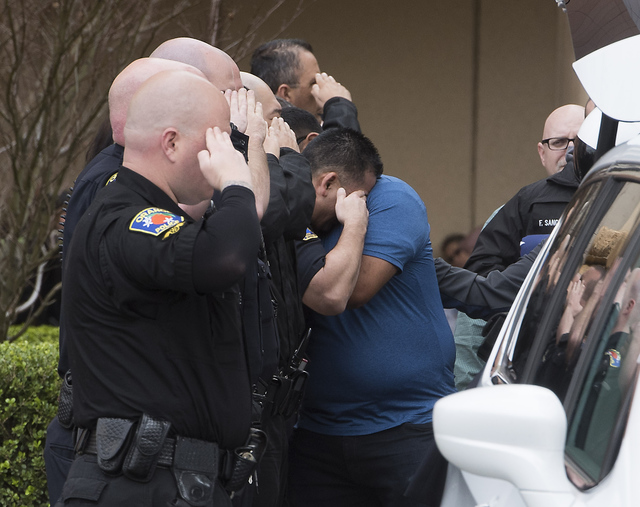 One police officer in the honor procession leans down to hug a man while still holding his salute as police officers turn out for a procession of honor at UCI Medical Center in Orange, Calif., Mon ...
