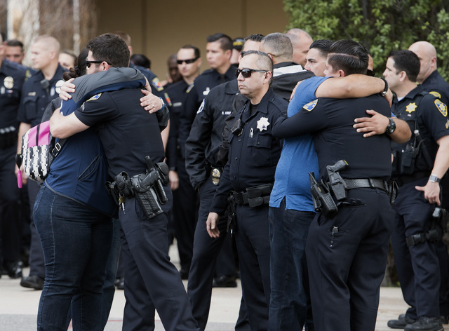 Police officers hug family members after police turned out for a procession of honor at UCI Medical Center for a fallen officer at at UCI Medical Center in Orange, Calif., Monday, Feb. 20, 2017. A ...