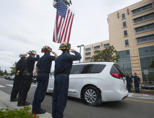 Anaheim firefighters form a line and salut as the escort for a slain officer drives by in Orange, Calif., Monday, Feb. 20, 2017. A California police officer was killed and another wounded in a sho ...