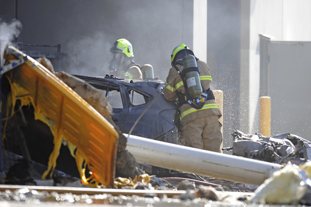 Emergency personnel work at the sight of a plane crash in Melbourne, Australia, Tuesday, Feb. 21, 2017. The plane crashed into a shopping mall, officials said. Five people including four Americans ...