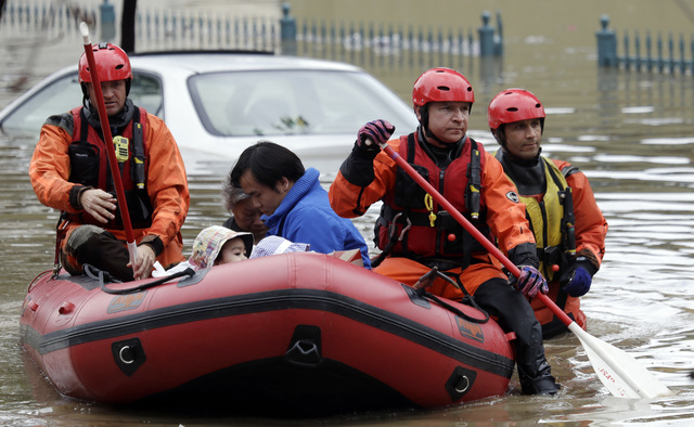 Rescue crews take out residents from a flooded neighborhood Tuesday, Feb. 21, 2017, in San Jose, Calif. Rescuers chest-deep in water steered boats carrying dozens of people, some with babies and p ...