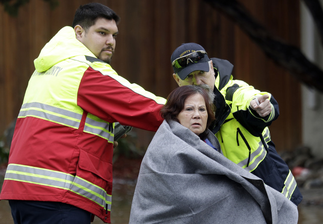 A woman is directed to a safe zone by rescue crews after being rescued by boat from a flooded neighborhood Tuesday, Feb. 21, 2017, in San Jose, Calif. Rescuers chest-deep in water steered boats ca ...