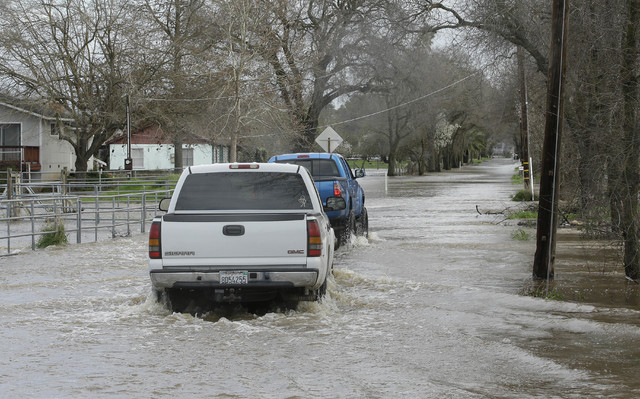 A pair of pickup trucks drive through flood waters covering Cherry Lane, Tuesday, Feb. 21, 2017, in Rio Linda, Calif. Water overflowing from nearby Dry Creek caused officials to call for voluntary ...