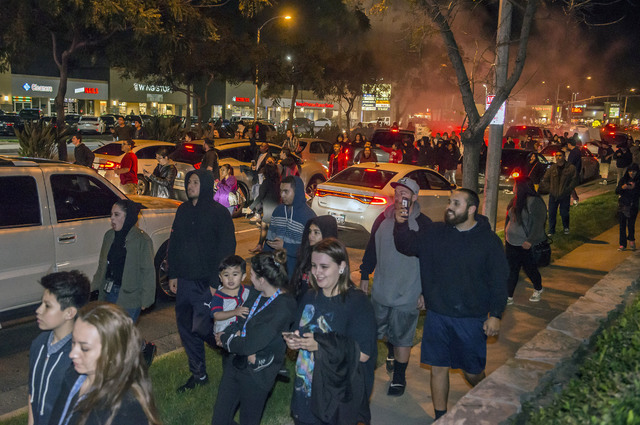 Protesters then took to Euclid Street, blocking traffic and marching north toward Ball Road, where they congregated in the intersection for several minutes in Anaheim, California, Wednesday, Feb.  ...