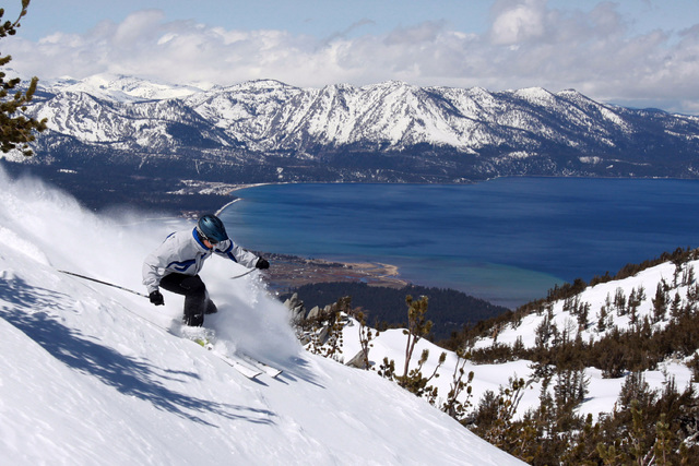 With Lake Tahoe as a backdrop, a skier kicks up some powder at Heavenly Ski Resort, Wednesday, April 14, 2010 in South Lake Tahoe, Calif.  (Dino Vournas/AP)