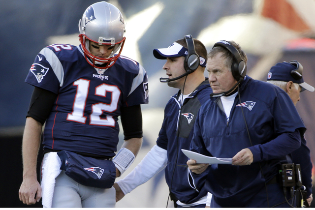 New England Patriots quarterback Tom Brady (12) listens to offensive coordinator Josh McDaniels, middle, and head coach Bill Belichick during the first half of an NFL football game against the Los ...