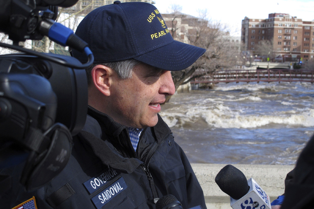 Nevada Gov. Brian Sandoval talks to reporters Monday, Jan. 9, 2017, in Reno, Nev., atop one of the downtown bridges across the Truckee River that remained closed after floodwaters crested earlier  ...