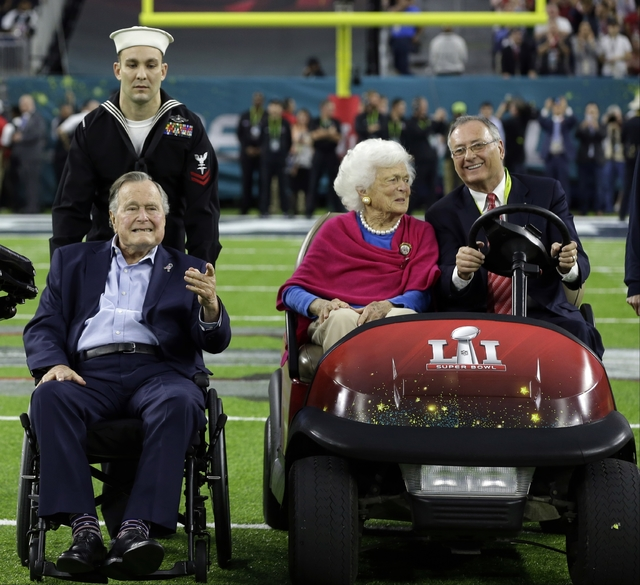 Former President George H.W. Bush and wife, Barbara, wave as they arrive on the field for a coin toss before the NFL Super Bowl 51 football game between the Atlanta Falcons and the New England Pat ...