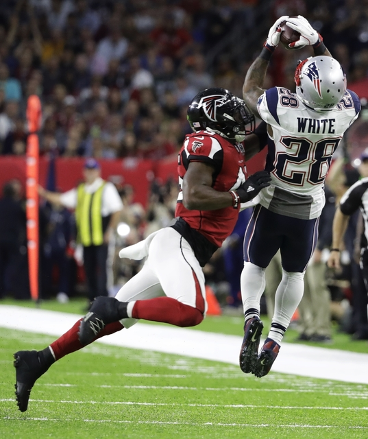 New England Patriots' James White, right, catches a pass under pressure by Atlanta Falcons' Deion Jones during the first half of the NFL Super Bowl 51 football game Sunday, Feb. 5, 2017, in Housto ...