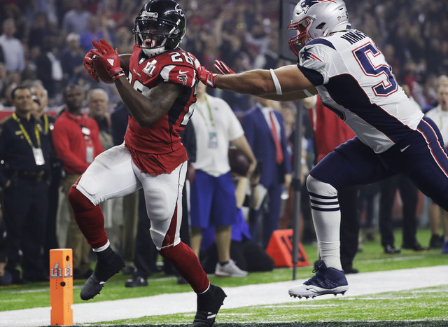 Atlanta Falcons' Tevin Coleman, left, scores past New England Patriots' Rob Ninkovich during the second half of the NFL Super Bowl 51 football game Sunday, Feb. 5, 2017, in Houston. (AP Photo/Chuc ...