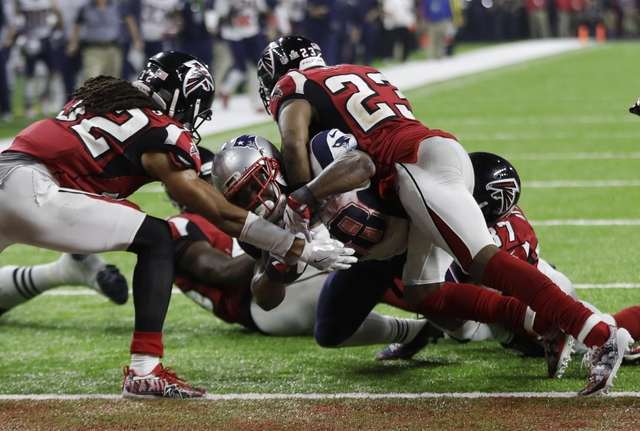 New England Patriots' James White scores the winning touchdown between Atlanta Falcons' Jalen Collins, left, and Robert Alford during overtime of the NFL Super Bowl 51 football game Sunday, Feb. 5 ...