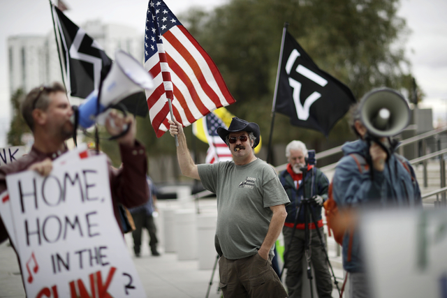 Greg Whalen, center, holds a flag in support of defendants on trial at the federal courthouse, Monday, Feb. 6, 2017, in Las Vegas. Jury selection began Monday in Nevada for the federal trial of si ...