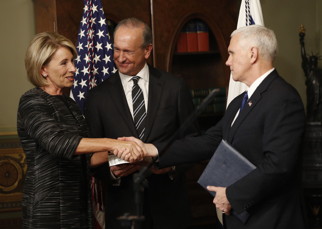 Vice President Mike Pence shakes hands after swearing in Education Secretary Betsy DeVos in the Eisenhower Executive Office Building in the White House complex in Washington, Tuesday, Feb. 7, 2016 ...