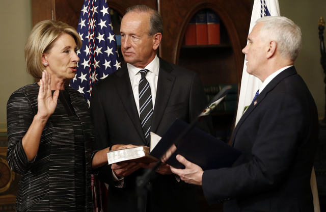 Vice President Mike Pence swears in Education Secretary Betsy DeVos in the Eisenhower Executive Office Building in the White House complex in Washington, Tuesday, Feb. 7, 2016, as DeVos' husband D ...