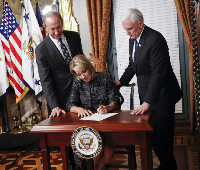 Vice President Mike Pence, right, watches as newly sworn in Education Secretary Betsy DeVos, center, signs the affidavit of appointment in the Eisenhower Executive Office Building in Washington, T ...