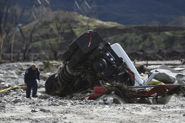 An official looks over the scene, Saturday, Feb. 18, 2017,  where a tractor trailer and a San Bernardino County Fire Department fire engine fell Friday from southbound Interstate 15 where part of  ...