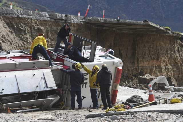 Officials look over the scene where a San Bernardino County Fire Department fire engine fell Friday from southbound Interstate 15 where part of the freeway collapsed due to heavy rain in the Cajon ...