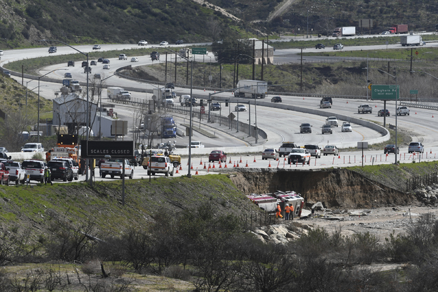 Traffic passes along the scene , Saturday, Feb., 18, 2017, where a tractor trailer and a San Bernardino County Fire Department fire engine fell on Friday from southbound Interstate 15 where part o ...