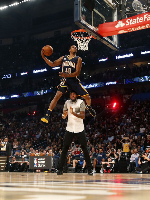 Indiana pacers Glenn Robinson III slam dunks over teammate Paul George as he participates in the slam dunk contest during NBA All-Star Saturday Night events in New Orleans, Saturday, Feb. 18, 2017 ...