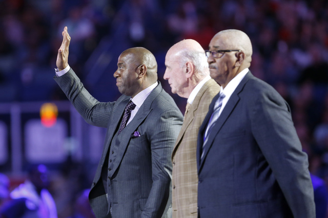 NBA Legend Magic Johnson waves as he is introduced with fellow legends Bob Pettit and Willis Reed, right, during the first half of the NBA All-Star basketball game in New Orleans, Sunday, Feb. 19, ...
