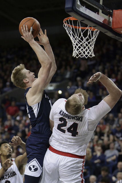 BYU forward Eric Mika, left, is fouled by Gonzaga center Przemek Karnowski (24) while shooting during the second half of an NCAA college basketball game in Spokane, Wash., Saturday, Feb. 25, 2017. ...