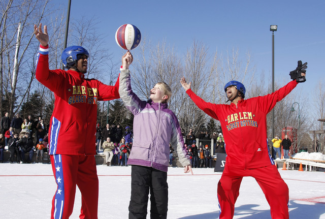 The Harlem Globetrotters seen at Globetrotters Play Basketball On Ice on Monday, Jan. 7, 2013 in Portage, MI. Harlem Globetrotter Scooter Christensen (l) spins the ball on the finger of 10-year ol ...