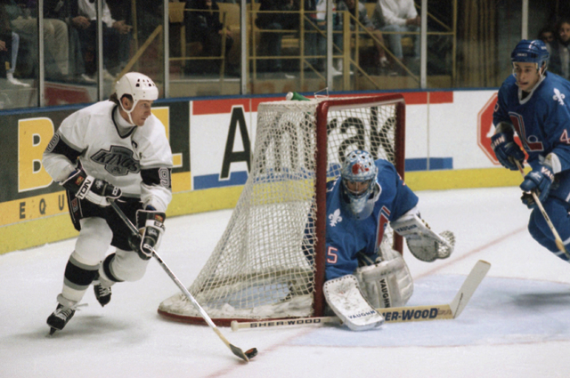Los Angeles Kings center Wayne Gretzky, left, maneuvers the puck as Quebec Nordiques goalie Stephane Fiset covers the goal in the first period of Tuesday's NHL game at the Forum in Inglewood, Cali ...