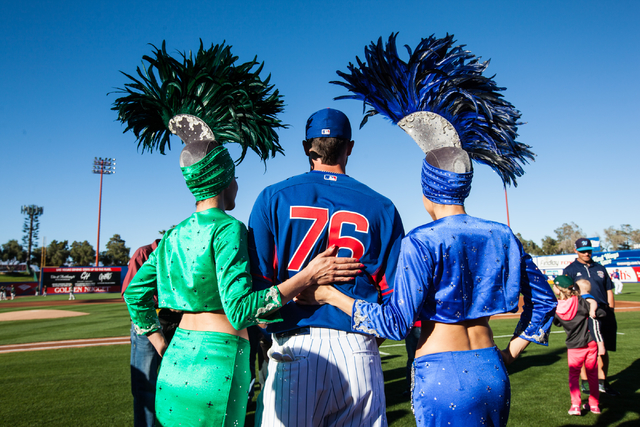 Kris Bryant of the Chicago Cubs poses for photos with showgirls before playing the Oakland Athletics in the Big League Weekend exhibition baseball game at Cashman Field in Las Vegas on Friday, Mar ...