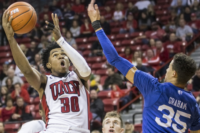 UNLV's Jovan Mooring (30) slashes to the basket over Air Force's Hayden Graham (35) during the Rebels home matchup with the Falcons on Saturday, Jan. 21, 2017, at the Thomas & Mack Center, in  ...