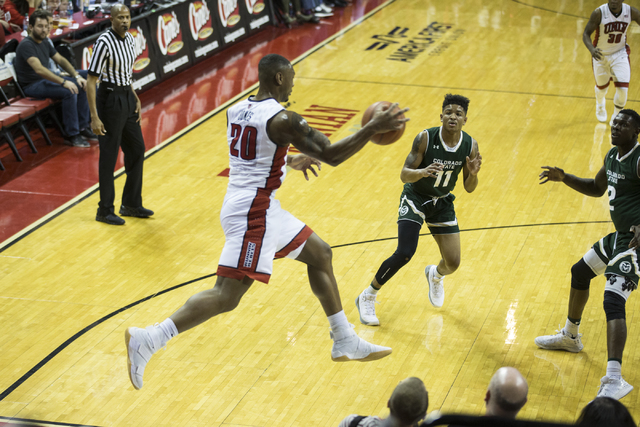 UNLV Rebels forward Christian Jones (20) attempts to save the ball from going out of bounds as Colorado State Rams guard Prentiss Nixon (11) and Emmanuel Omogbo (2) look on in their men's basketba ...