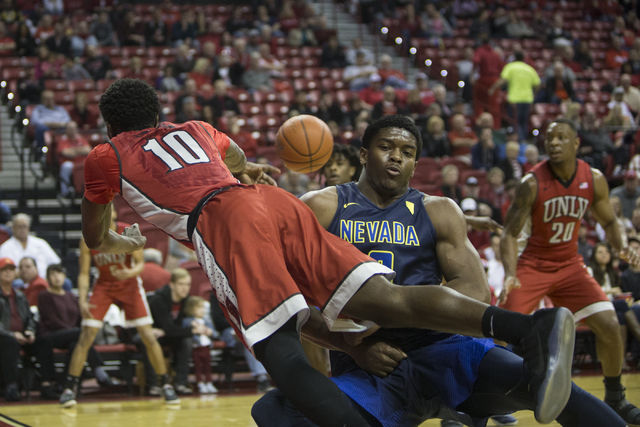 UNLV Rebels guard Zion Morgan (10) makes a pass as he  falls to the ground against Nevada Wolf Pack forward Cameron Oliver (0) in their basketball game at the Thomas & Mack Center on Saturday, ...