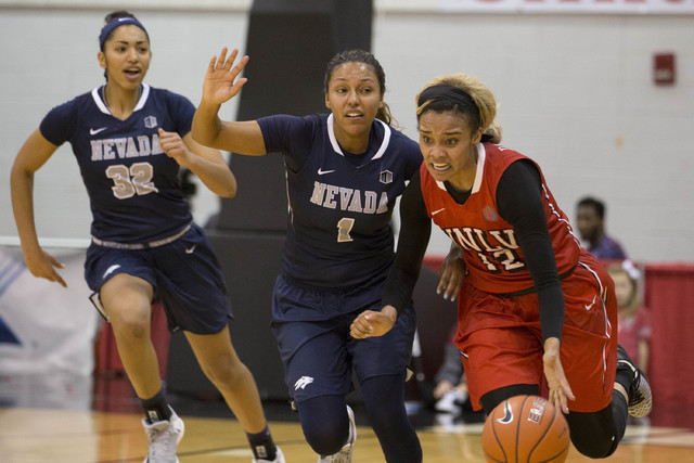 UNLV Rebels guard Dakota Gonzalez (12) takes the ball to the basket with Nevada Wolf Pack guard Ashlee Jones (1) and forward AJ Cephas (32) close behind at Cox Pavilion at UNLV campus on Wednesday ...