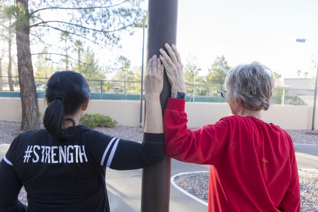 Lara Ceccarini, left, personal trainer, and Carolyn Bruce, a baby boomer living at the Mountain Shadows Community Center, stretch their arms after completing their workout agenda outside of the co ...