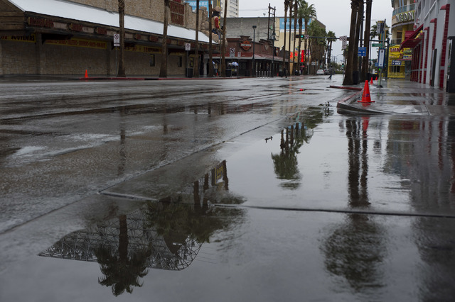 Puddles fill the street on Saturday, Feb. 18, 2017, in downtown Las Vegas. On Friday a flash-flood watch for Southern Nevada that will last through Saturday evening was issued by weather service . ...